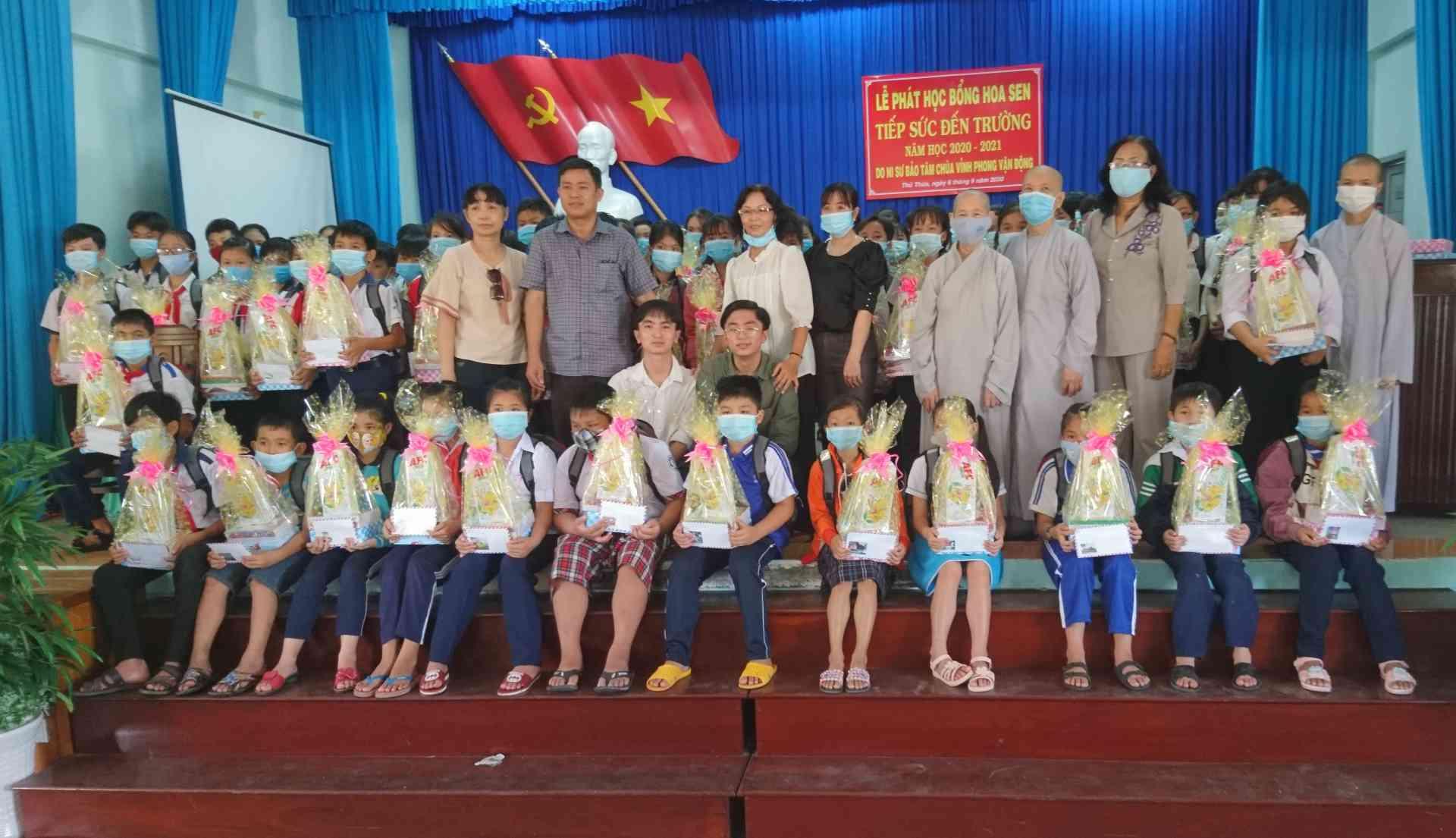 Lãnh đạo huyện và Ban tổ chức chụp ảnh lưu niệm với học sinh nhận quà